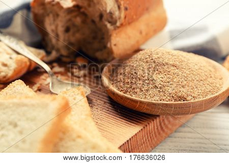 Fresh bread crumbs on wooden board closeup