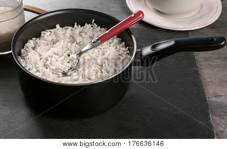 Cooked rice in saucepan with spoon on slate board