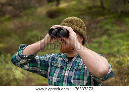 Red haired man looking throw a binocular in the field