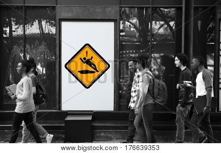 Group of People Walking with Slip Caution Sign Banner Behind
