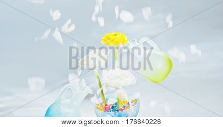 Flowers in a glass vase with multi-colored gel balls and two levitating glass jars on a light background with floral petals