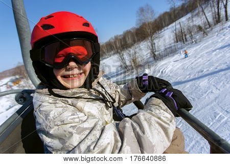 Girl skier in a red helmet and goggles on a lift in a ski resort