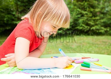 Portrait of cute blond girl wearing red tshirt sitting at a table in a summer garden drawing with felt-tip pens