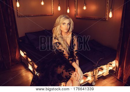 Young attractive woman in black negligee posing on bed.