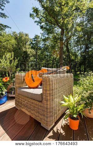 Guitar On A Garden Sofa During Sunny Day