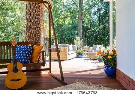 A Guitar Standing Beside A Garden Swing