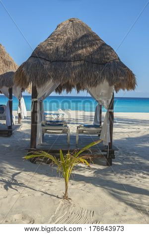 Loungers under hut canopy on a Caribbean beach in Cancun Mexico