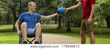Man On A Wheelchair Taking Ball