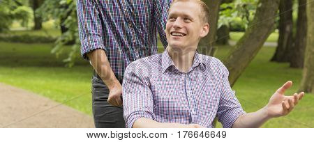 Man Pushing The Wheelchair With His Friend