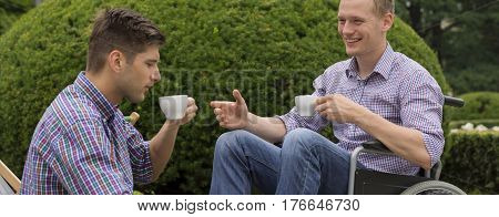 Man On A Wheelchair Drinking With Friend