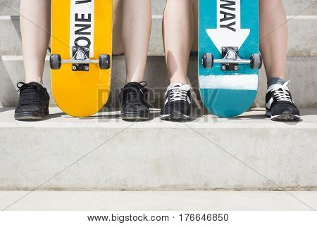 Closer shot of two women's legs with the skateboards leaned on the stairs