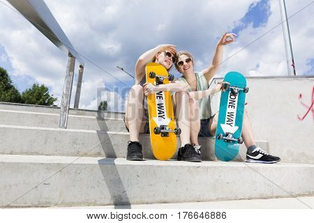 Young Girls Sitting On The Stairs With Skateboards