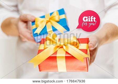 Male hands holding a gift boxes. Present wrapped with ribbon and bow. Gift for you speech bubble. Man in white shirt.