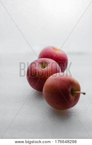 Three red small and delicious apples in white background