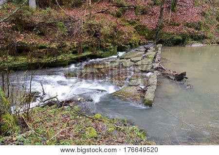 Small waterfall on a stone dam of a small stream in Luxembourg