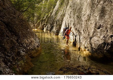 Man walks through the narrow mountain canyon river with his shoes in his hand. Grand canyon, Crimea