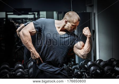Bodybuilder showing off his pumped hand in poses the weightlifter demonstrates his biceps powerlifting man strains the biceps pumped-up body of a huge bodybuilder strong man show his hands muscles.