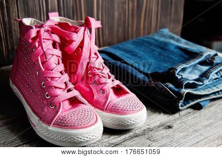 A Pink Shiny Shoes And Blue Jeans For Girls On A Wooden Background