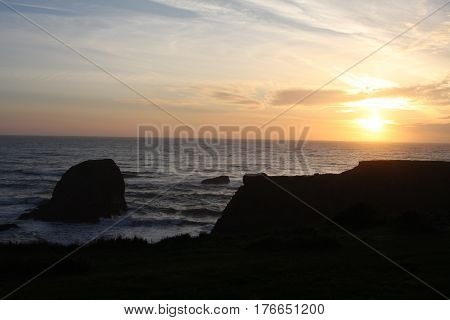 A golden setting sun inches near the crisp horizon of blue-grey ocean. A silhouetted foreground makes excellent space for a message or text to be added.