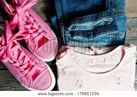 Denim Trousers With Light Top And Pink Canvas Shoes. Light Denim Shorts On Table.