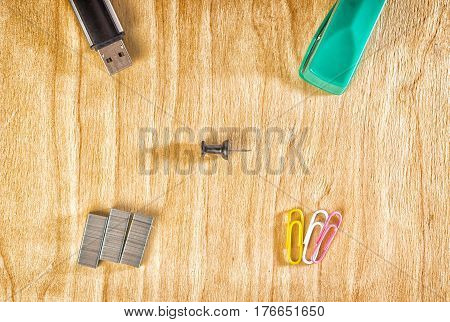 Office accessories on a wooden background stapler paper clips and a flash drive for storing information