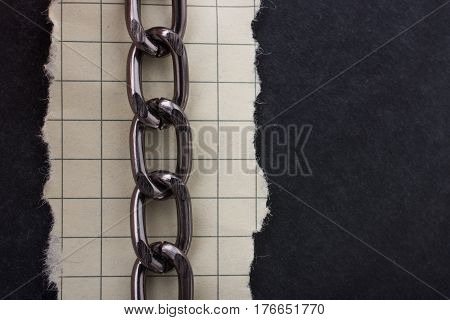 Chain And Torn Paper On Dark Background