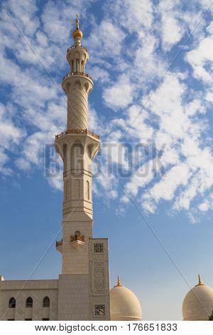 Sheikh Zayed Mosque minaret on the background of cloudy blue sky Abu Dhabi UAE - famous tourist destination.
