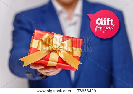 Male hand holding a gift box. Present wrapped with ribbon and bow. Gift for you speech bubble. Man in suit and white shirt.