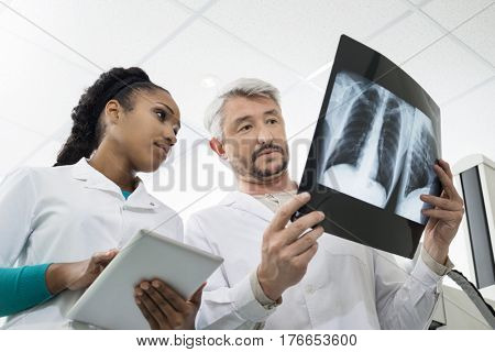 Radiologists With X-ray Using Digital Tablet In Hospital
