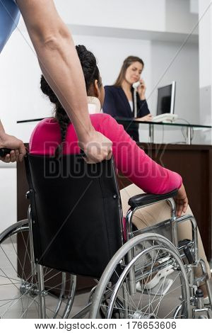 Doctor Pushing Patient On Wheelchair While Receptionist Working