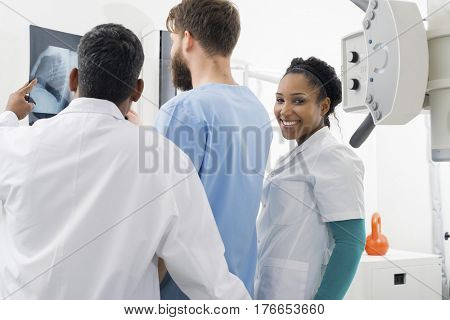 Female Radiologist With Colleagues Analyzing X-ray In Hospital