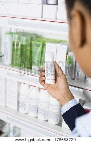 Businesswoman Reading Instructions On Medicine Bottle At Pharmacy
