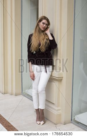Portrait full length of young beautiful blonde woman in white pants and corduroy jacket