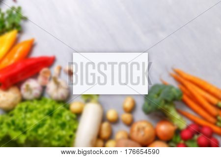 Business card mockup. Vegetables. Potatoes, onion and garlic. Pepper, brocoli and green salad. Celery, carrot and radish. Organic vegetables.