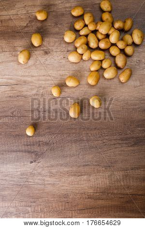 Potatoes on wooden table. Raw new potato. Fresh natural vegetables. Organic bio food on rustic background.