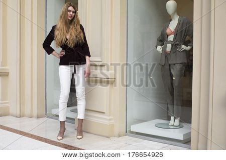 Full-length portrait, young beautiful blonde woman in white pants and corduroy jacket stands in the shop window