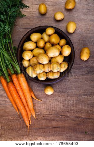 Potatoes in a rustic plate. Carrot and raw new potato. Fresh natural vegetables. Organic bio food on wooden table.