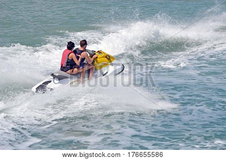 Young couple riding tandem on a jet ski on the florida intra-coastal waterway a popular activity especially on week-ends.
