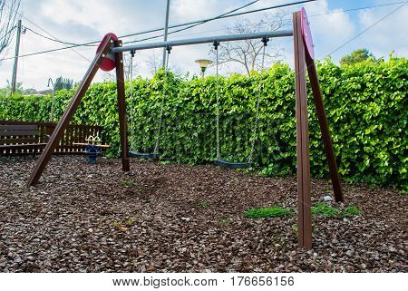 Empty swings with chains swaying at playground for child, ivy on the background