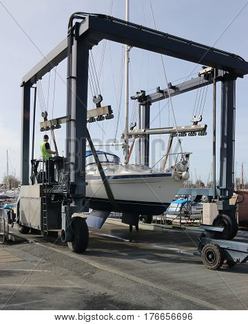 14TH MARCH 2017,CHICHESTER,ENGLAND: A yacht getting ready to be lowered into the water using a boat cradle sling in chichester marina ,england on the 14th march 2017