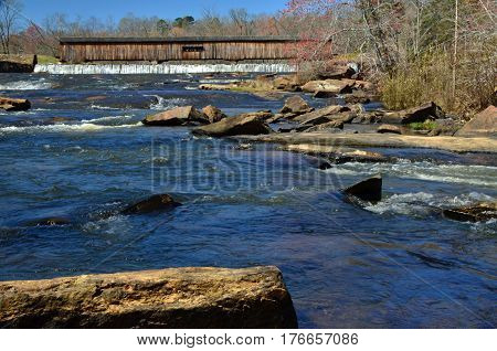 Rocky waters along the covered bridge at Watson Mill State Park in Comer, Georgia
