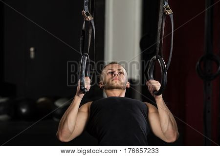 Fitness Man Exercising On Gymnastic Rings In The Gym