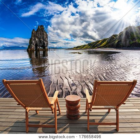 Two wooden deck chairs are on the beach. Magic Rock Hvitsercur on Northern coast of Iceland. Concept of extreme northern tourism