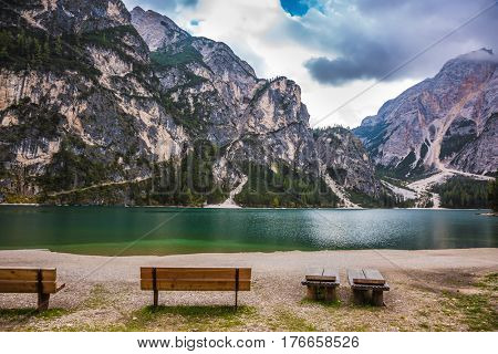 Two benches at the lake beach. Magnificent lake in South Tyrol, Italy. The concept of walking and eco-tourism. Water reflects the surrounding mountains and forest