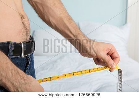 Close-up Of A Man Using Measuring Tape On Jean At Home