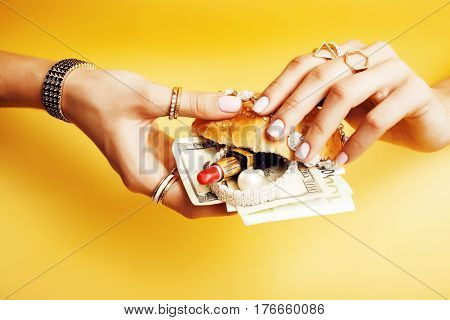 woman hands holding hamburger with money, jewelry, cosmetic, social issue wealth concept close up