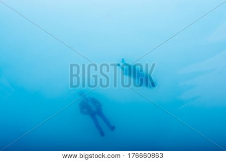 Man and woman figurine in blue water