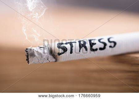 Close-up Of A Stress Word Written On Burning Cigarette