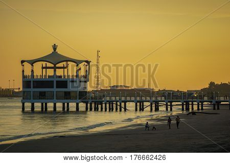 Labuan,Malaysia-Mac 15,2017:View of Manja Rasa floating restaurant during sunset with silhouette of people in the beach in Labuan island,Malaysia.