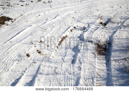 traces of the car in the snow in winter .